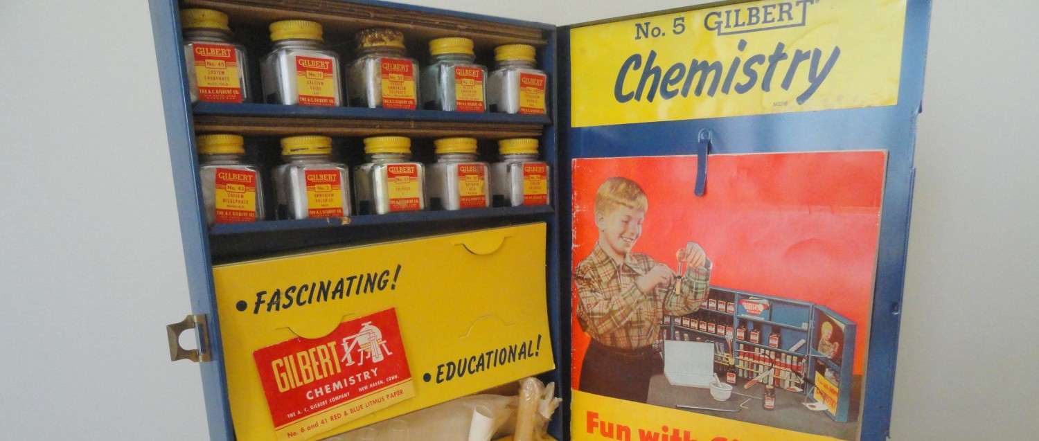 """The image features a vintage chemistry set in a blue metal case. On the top left are 10 glass bottles containing chemicals. Each features a red and yellow label. On the bottom left are pieces of glass and metal apparatus, such as test tubes and tongs. On the right there is a booklet that features a boy in a plaid shirt holding a test tube, with his chemistry set in the background. The booklet is titled """"Fun with Chemistry."""""""