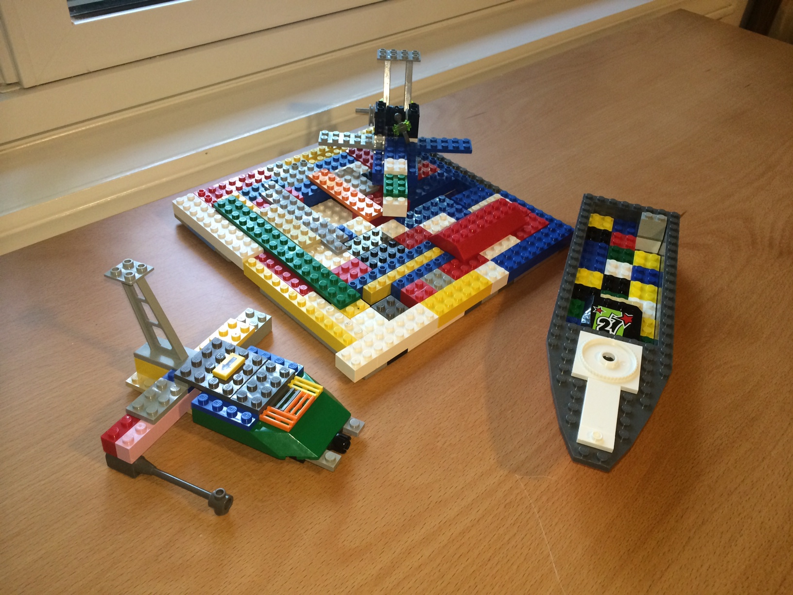 The picture depicts three LEGO compositions. On the left is a colorful airplane or spaceship; in the middle is another colorful airplane on a LEGO landing pad; to the right is a grey LEGO boat with a colorful floor.