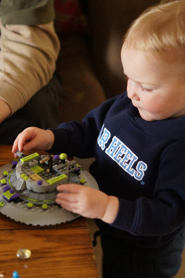 The image shows Caroline, a Caucasian, blonde-haired girl, wearing a navy blue Tarheels sweatshirt. She is touching the pieces on top of a gray and fluorescent green spaceship that is positioned on a table.