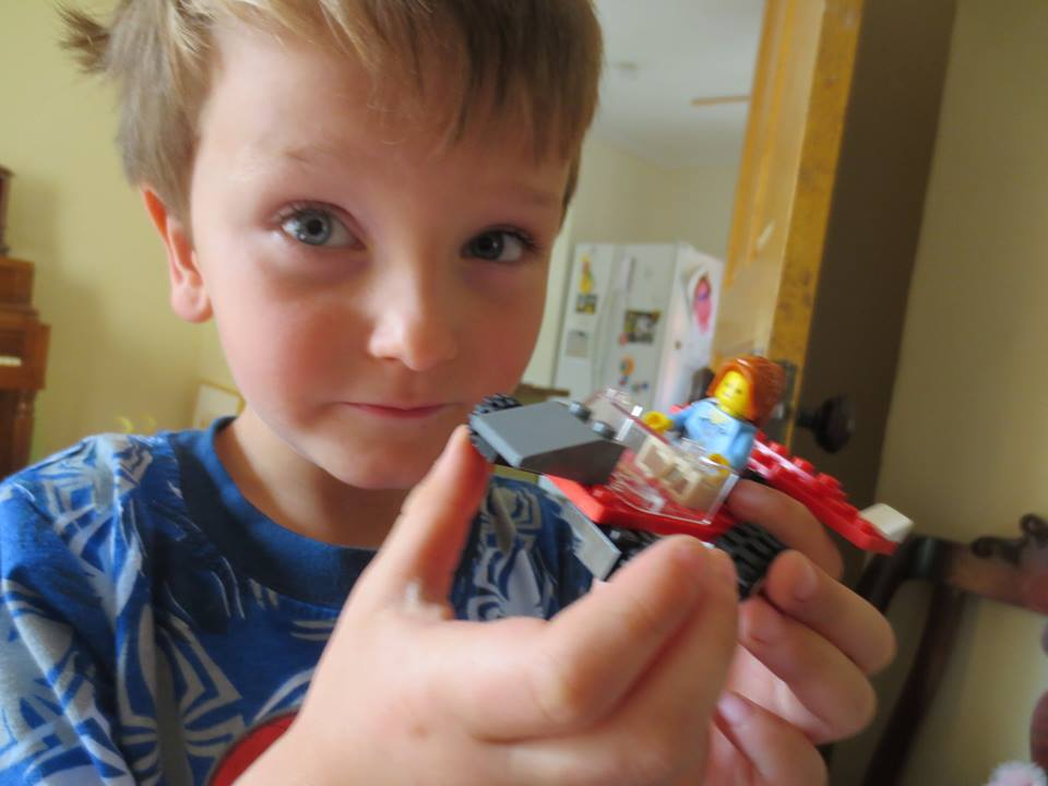This image features a five-year-old boy with blonde hair and blue eyes. He is holding up a spacecraft he has created out of Lego. The spacecraft is red and grey and features a female minifig (Lego person) with a blue shirt and red hair.