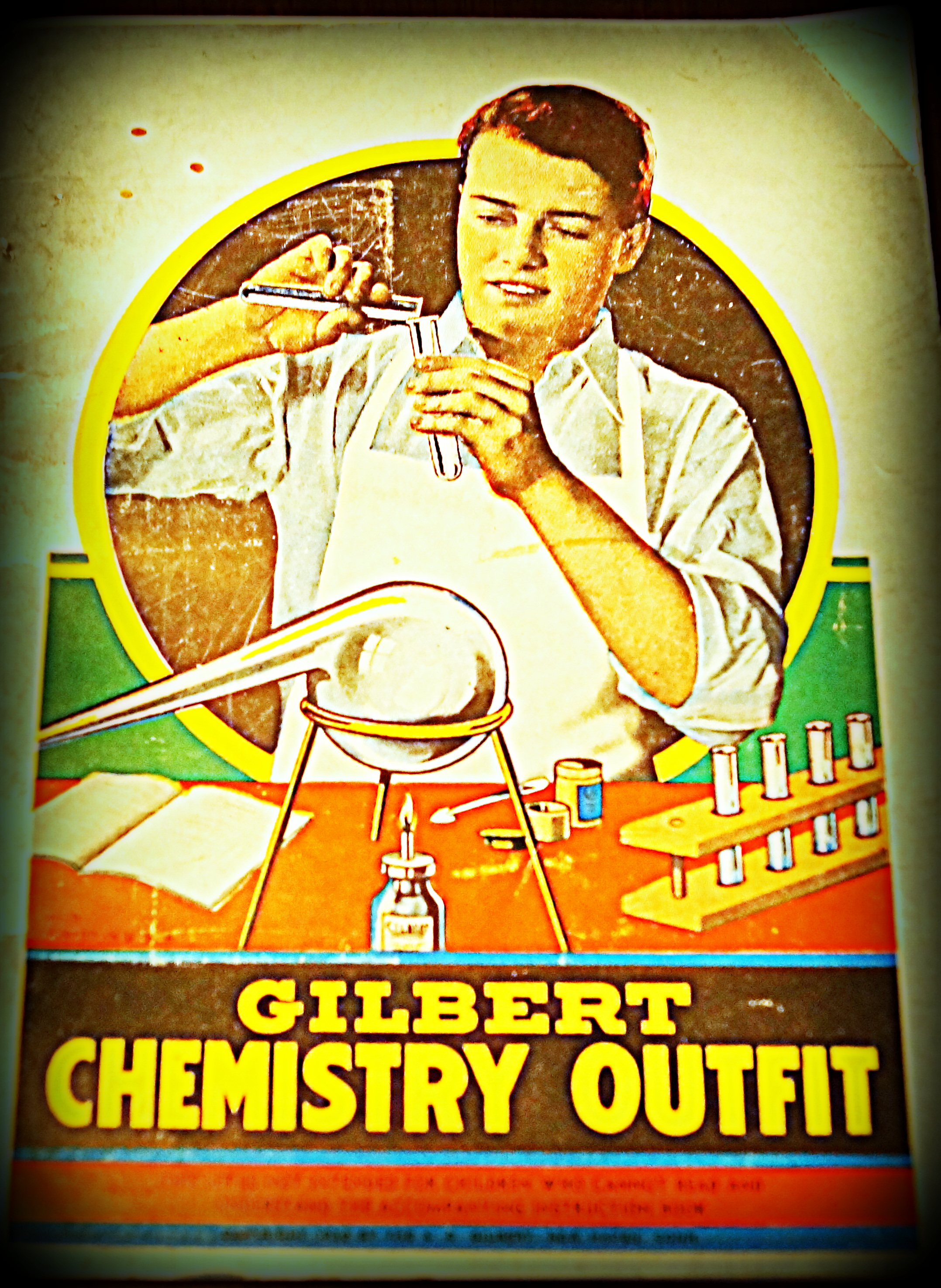 The image depicts the front cover of a Gilbert Chemistry Outfit instruction manual. On the cover, a young man is pictured in a white shirt and a white smock. He is pouring a chemical from one test tube into another. In front of him, on a desk, is displayed his apparatus, including a bunsen burner, a rack containing test tubes, and a spatula.