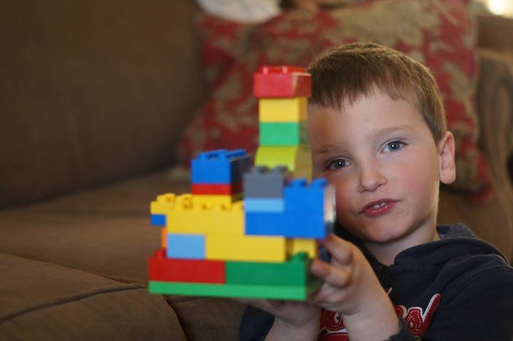 This photograph features a four-year-old male, Caucasian child holding a colorful composition he has made out of large Duplo blocks that are red, yellow, green, and blue. In the background we see a brown couch and red pillow.